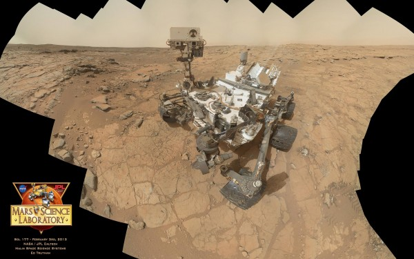 "NASA / JPL / MSSS / Ed Truthan Curiosity MAHLI self-portrait, sol 177 A total of 64 frames shot by the MAHLI on the end of Curiosity's robotic arm were required for this large mosaic. On sol 177 (February 3, 2013), the rover was sitting at the ""John Klein"" site, preparing to drill for the first time. Zoom in at lower left and you can see two gray marks on the ground where Curiosity tested out the drill in percussion mode on sols 174 and 176."
